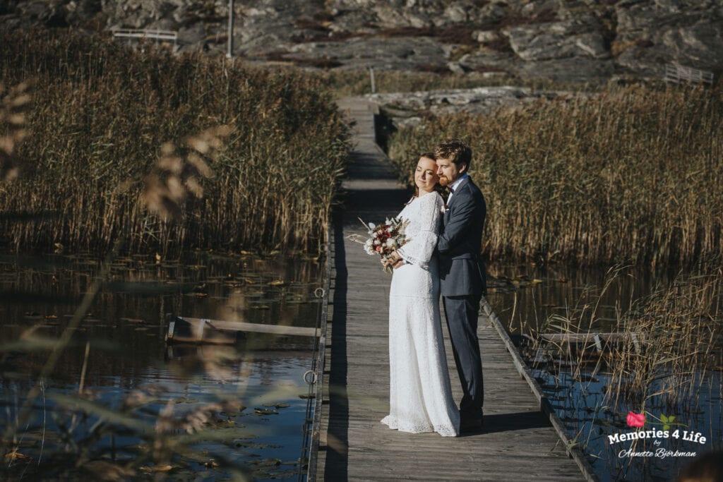 brudparet håller om varandra på en lång brygga i vattnet