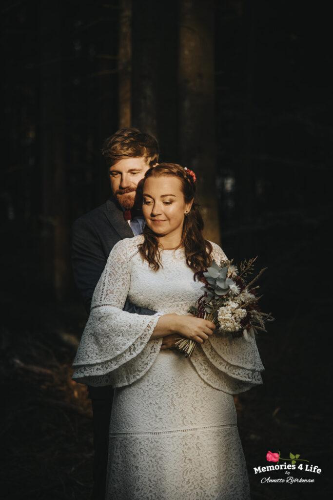 brudgummen står bakom bruden och kramar om henne