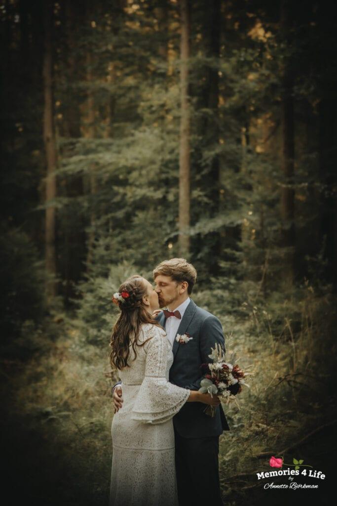 brudparet kysser varandra i skogen