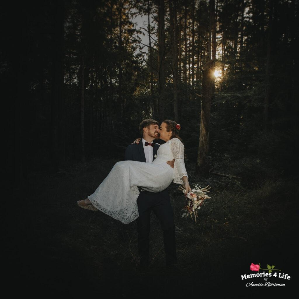 Brudgum lyfter brud i solnedgång