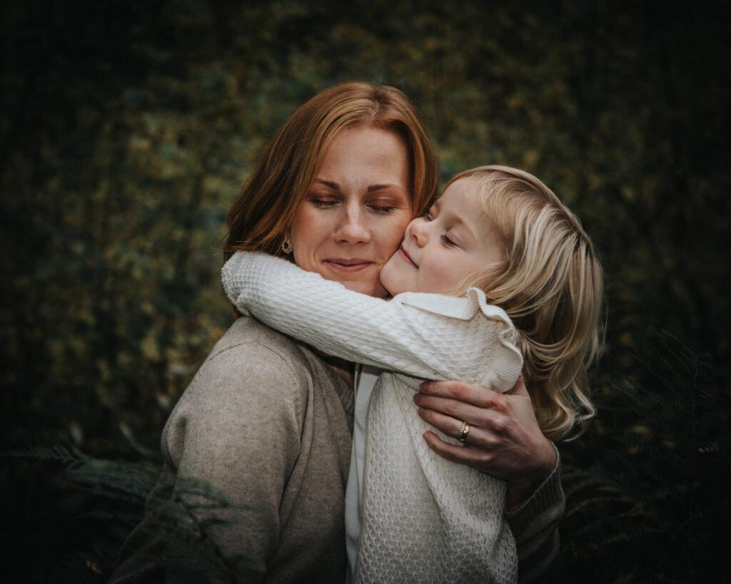 Mor och dotter blundar och kramas i skogen