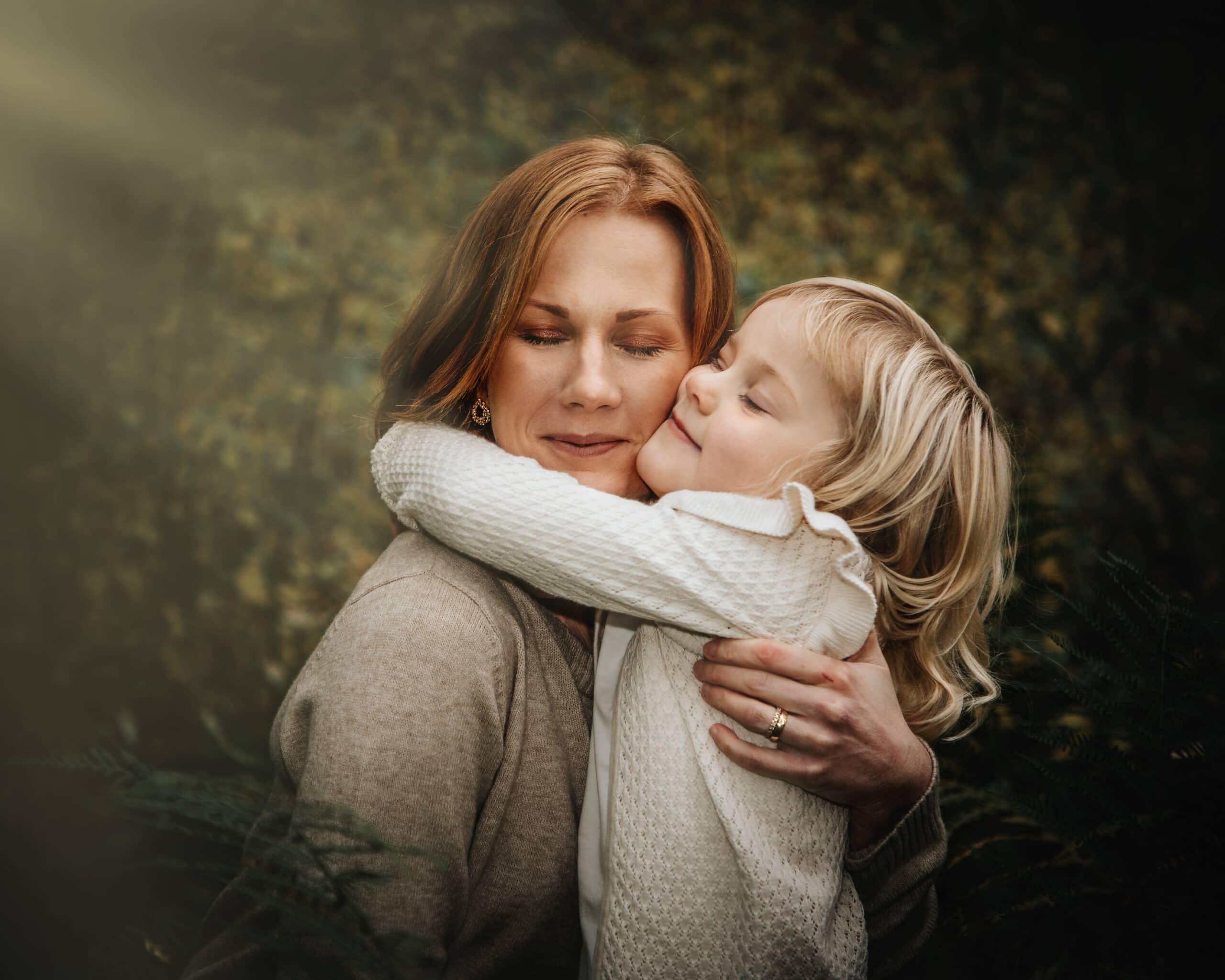 Mor och dotter blundar och kramas i skogen-Redigeringsbild