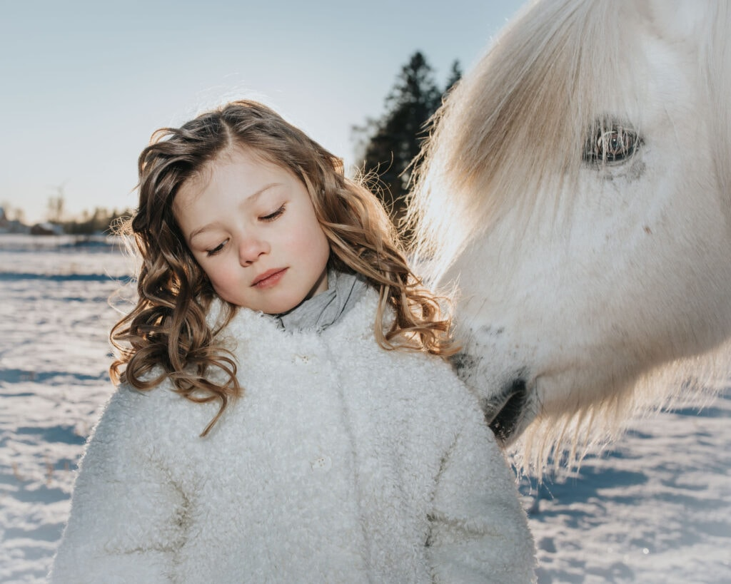 Flicka i Vinterlandskap med vit häst